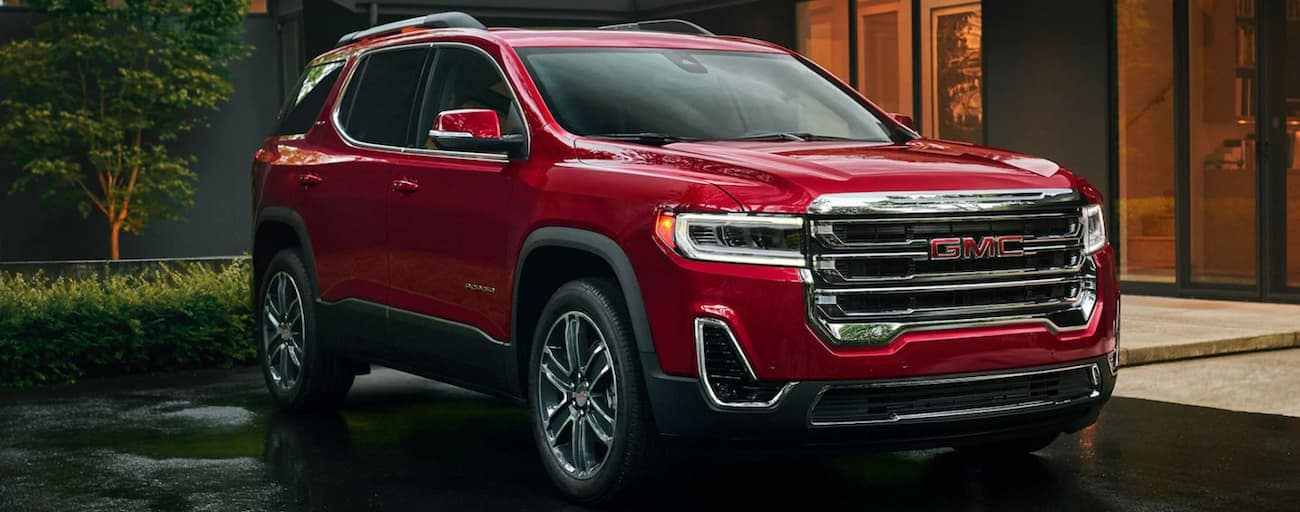 A red 2020 GMC Acadia is parked at an Atlanta, GA home's driveway on a rainy day.