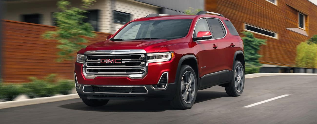 A red 2020 GMC Acadia is driving past a wooden building near Atlanta, GA.