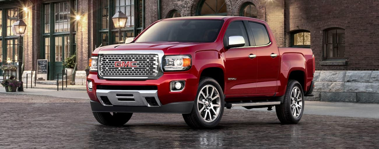 A red 2020 GMC Canyon is parked in front of a brick building near Atlanta, GA.