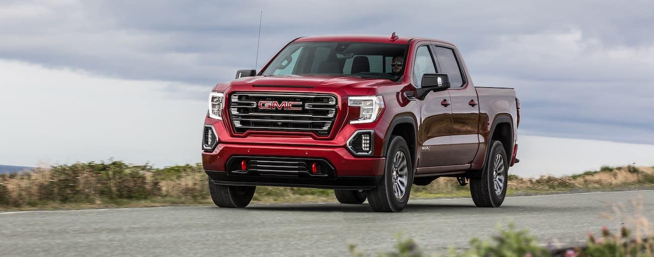 A red 2020 GMC Sierra 1500 AT4 is driving with clouds in the sky.