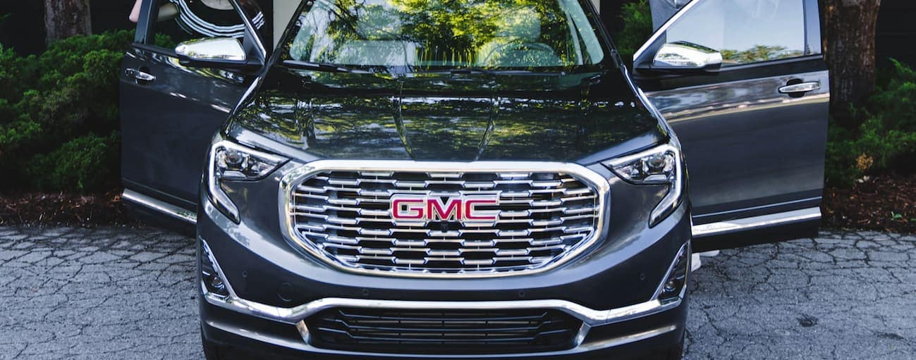 A close up of the end of a black 2020 GMC Terrain that has both front doors open is shown.