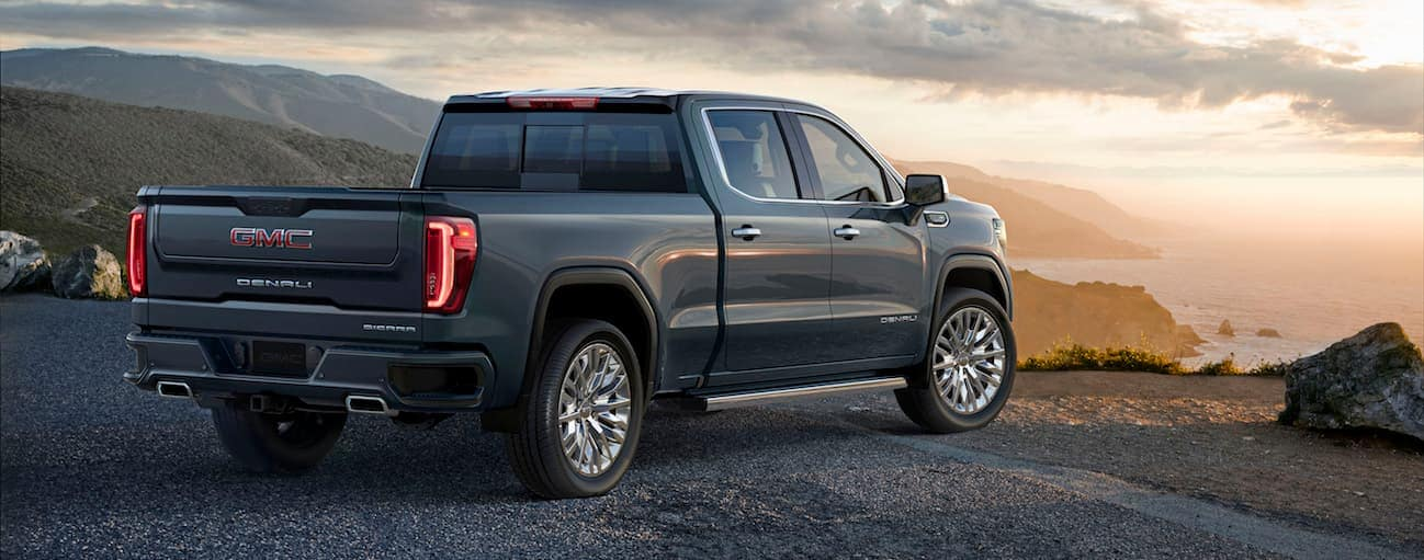 A blue 2020 GMC Sierra 1500 is parked in a dirt parking lot overlooking the ocean at dusk.
