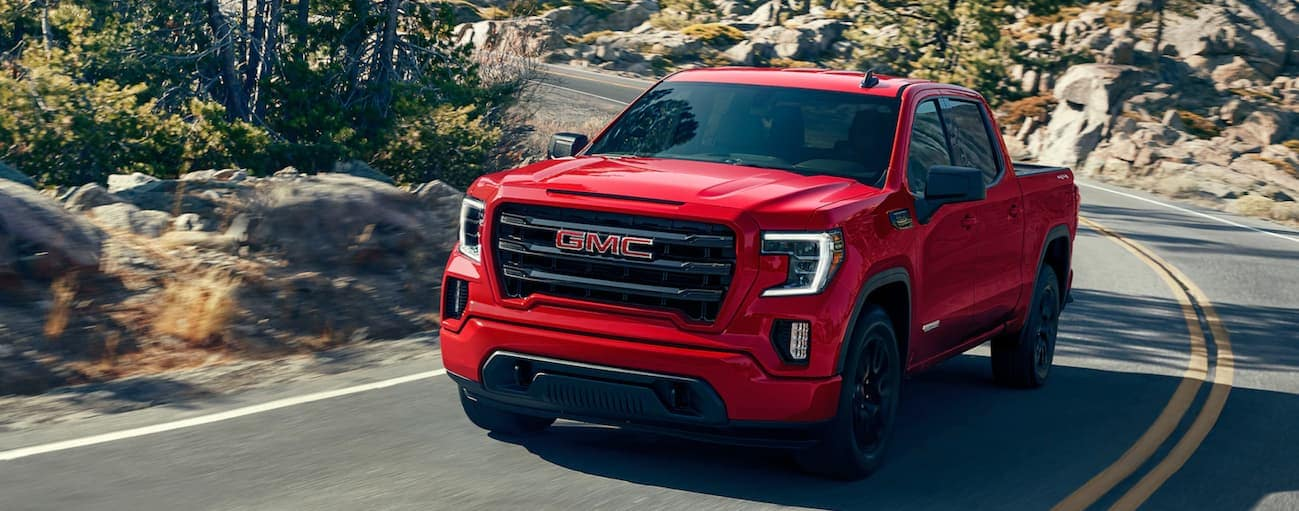 A red 2020 GMC Sierra 1500, which wins when comparing the 2020 GMC Sierra 1500 vs 2020 Ford F-150, is driving around a treelined corner near Atlanta, GA.