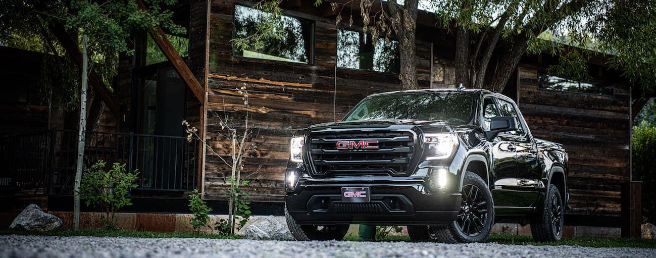 A black 2020 GMC Sierra 1500, which wins when comparing the 2020 GMC Sierra 1500 vs 2020 Ram 1500, is parked in front of a brown wooden home near Atlanta, GA.