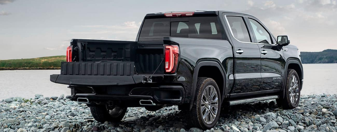 A black 2020 GMC Sierra 1500 has its tailgate down while parked on small rocks facing a lake.
