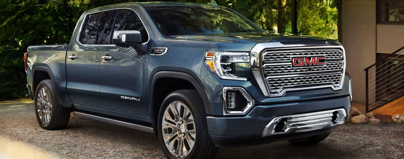 A blue 2020 GMC Sierra 1500 is parked in a gravel driveway next to an Atlanta, GA home.