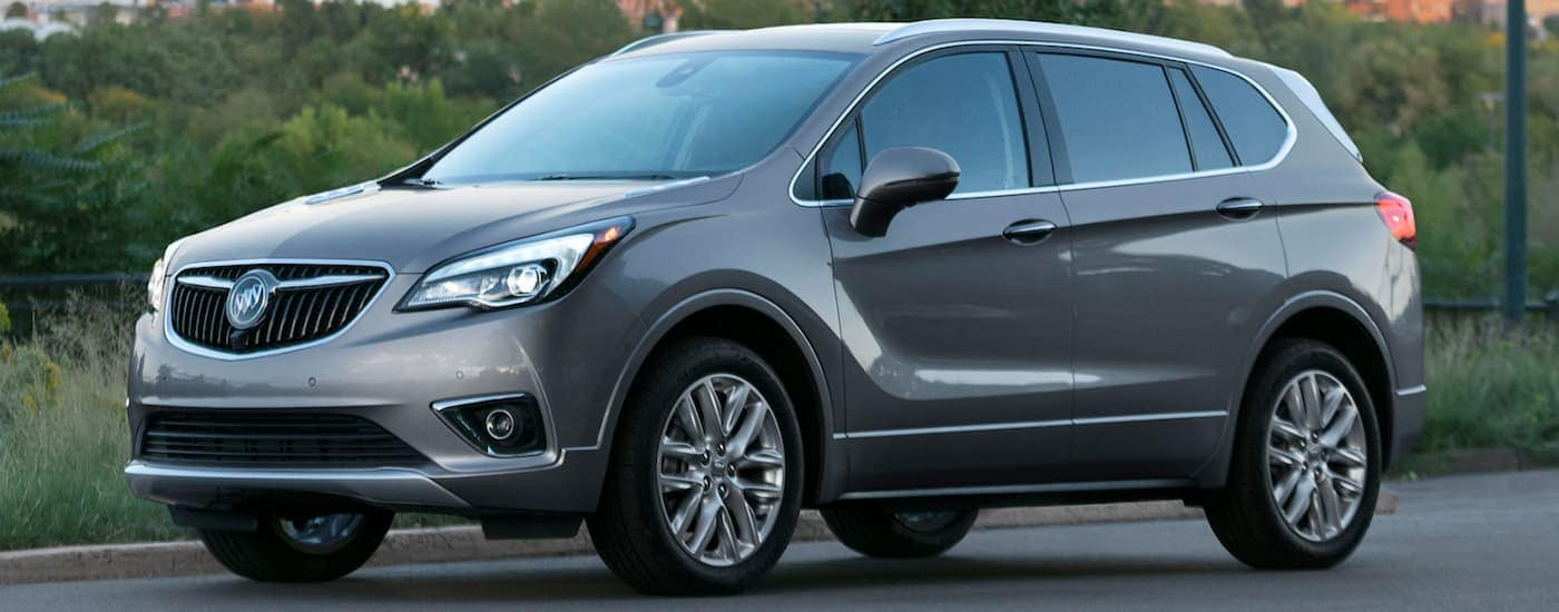 A grey 2020 Buick Envision, popular among the 2020 Buick SUVs, is parked next to trees with a city sky line in the distance.