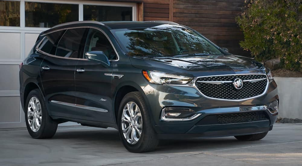 A blue 2020 Buick Enclave Avenir, a popular option among Buick SUVs, is parked in front of white garage at an Atlanta, GA, home.