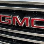 "A close up of a GMC truck grille is shown with red ""GMC"" lettering."