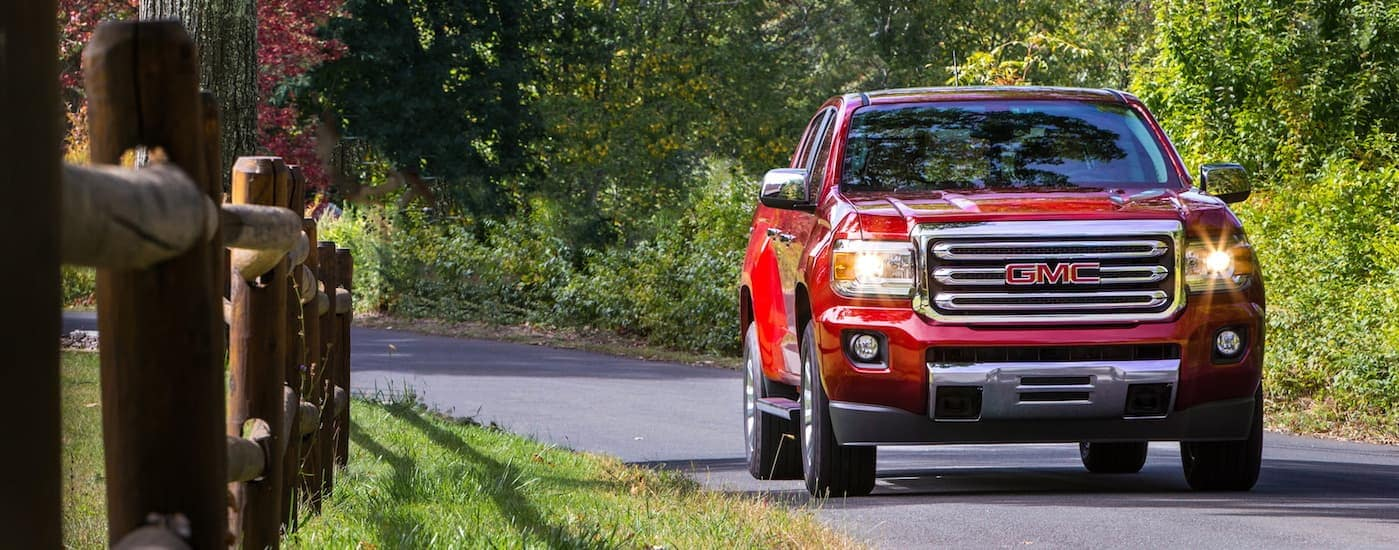 A red 2020 GMC Canyon, which is a popular option among GMC Trucks, is driving on a tree lined road near Atlanta, GA.