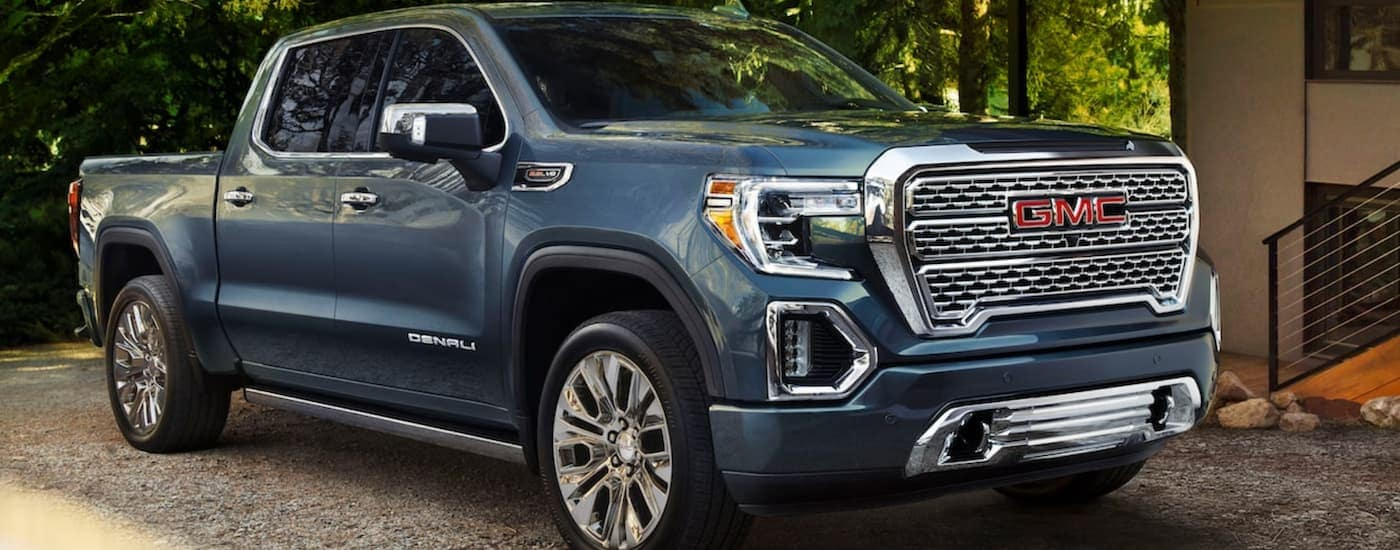A blue 2020 GMC Sierra 1500 is parked in a tree covered driveway in the shade.