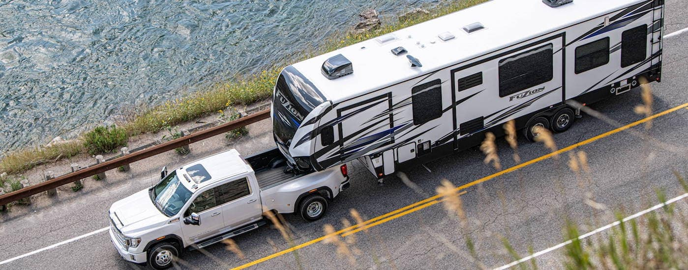 A white 2020 GMC Sierra 3500HD is towing a large RV trailer next to a lake.