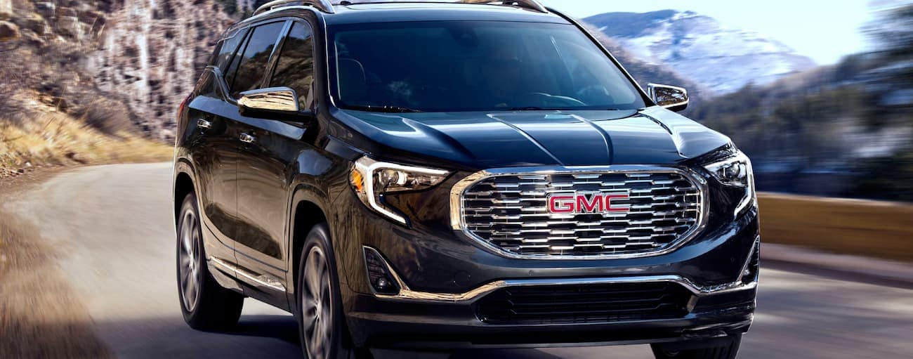 A black 2020 GMC Terrain, which wins when comparing the 2020 GMC Terrain vs 2020 Ford Escape, is driving on a roads with hills behind it.