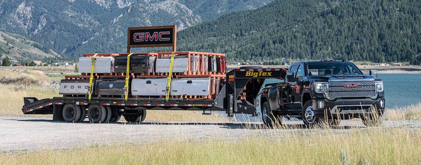 A black 2020 GMC Sierra 3500HD is towing a large trailer with heavy equipment on it with mountains in the distance.