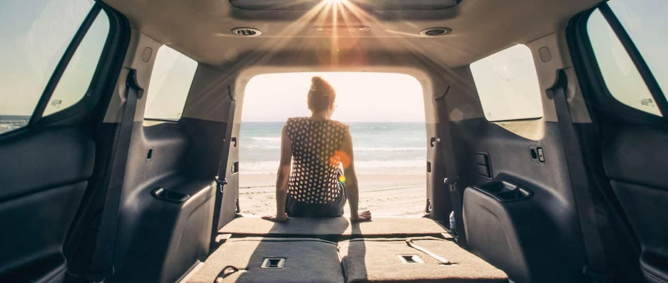 The backseats are down in a 2020 GMC Acadia while a woman looks out at a beach.