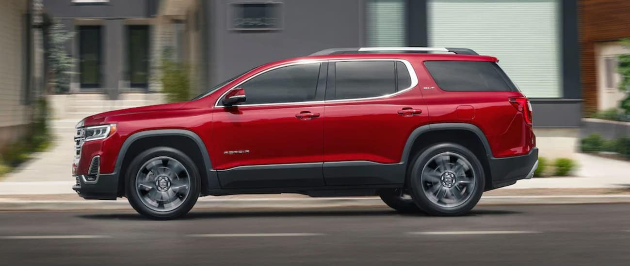 A red 2020 GMC Acadia, which wins when comparing the 2020 GMC Acadia vs 2020 Jeep Grand Cherokee, is driving past blurred buildings near Atlanta, GA.