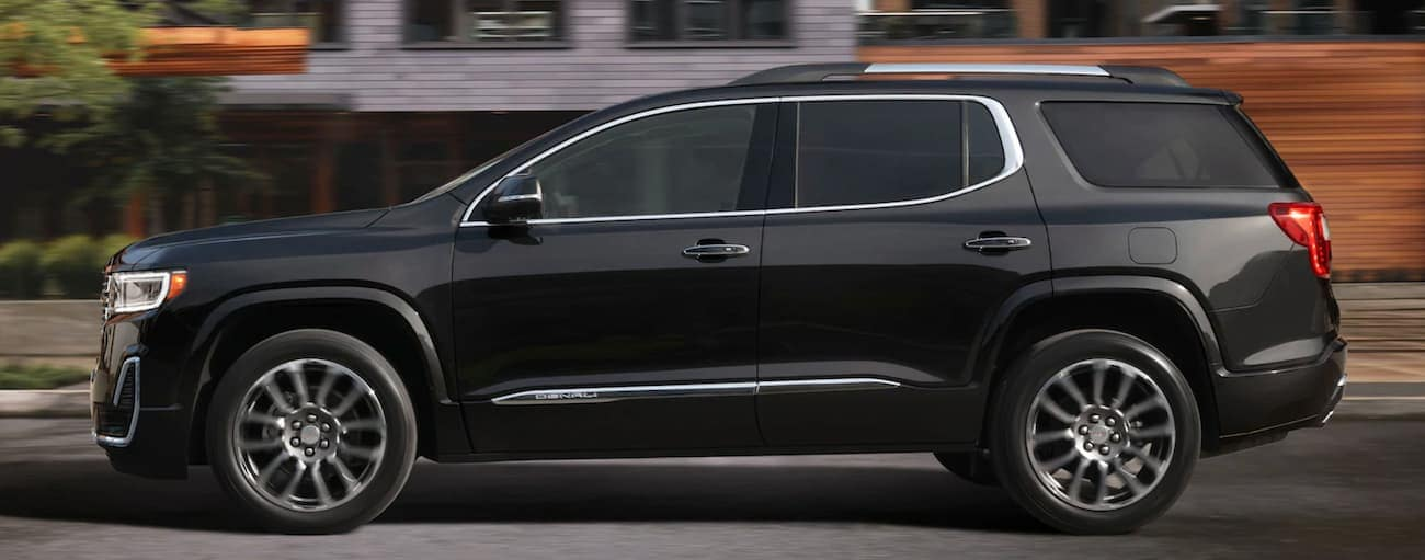 A black 2020 GMC Acadia is shown from the side while it's driving on a city street.
