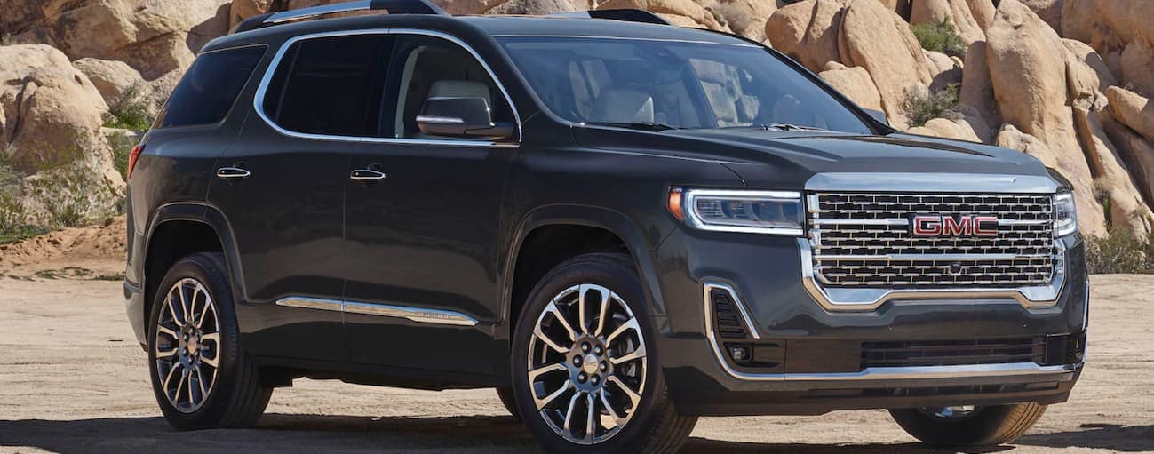 A dark grey 2020 GMC Acadia, which wins when comparing the 2020 GMC Acadia vs 2020 Kia Telluride, is parked on sand in front of a large rock wall near Atlanta, GA.