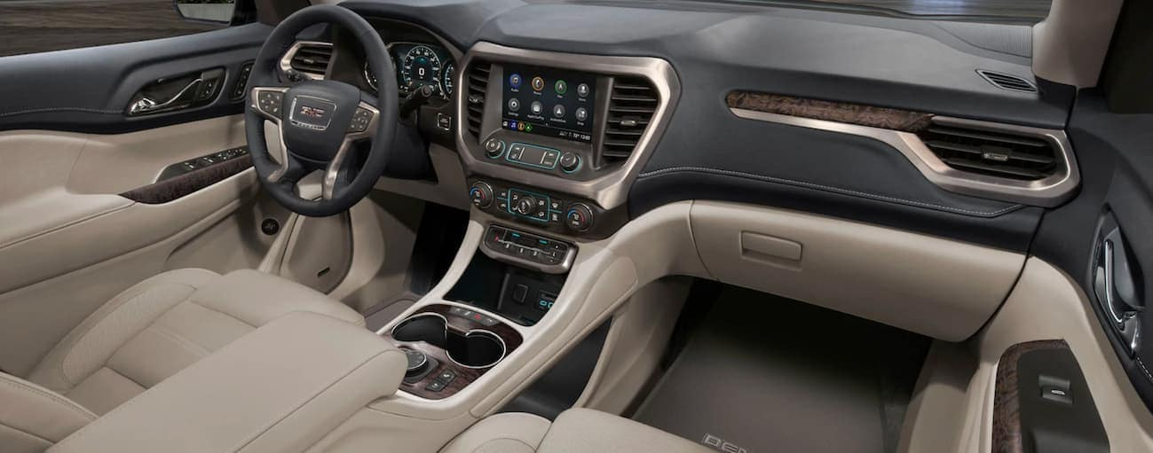 The front tan and grey interior of a 2020 GMC Acadia is shown.