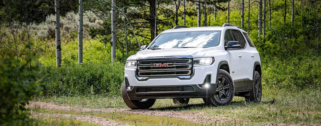 A white 2020 GMC Acadia AT4, which wins when comparing the 2020 GMC Acadia vs 2020 Nissan Pathfinder, is parked on a dirt trail near Atlanta, GA.