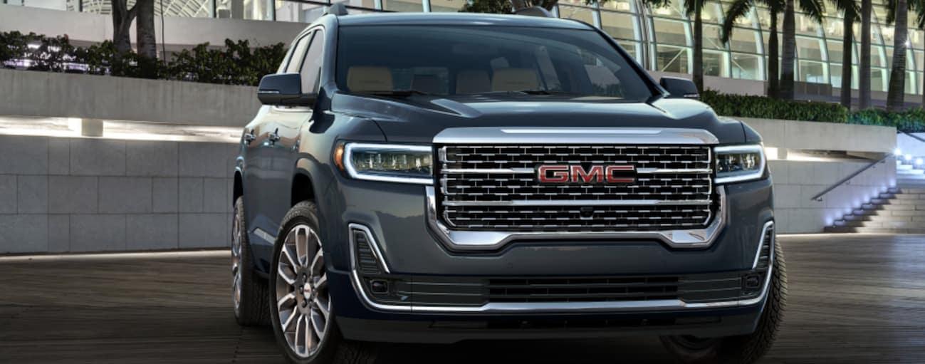 A grey 2020 GMC Acadia is parked in front of a  brick wall near Atlanta, GA.