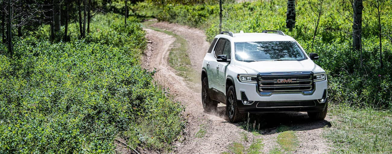 A white 2020 GMC Acadia AT4, which wins when comparing the 2020 GMC Acadia vs 2020 Toyota 4Runner, is off-roading on a dirt trail.