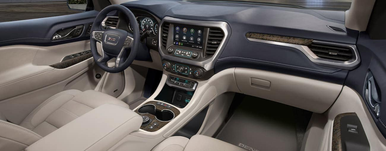 The black and cream interior of a 2020 GMC Acadia is shown.