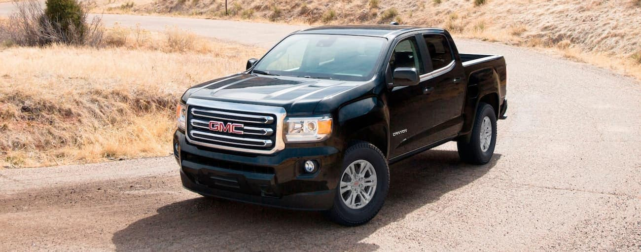 A black 2020 GMC Canyon is on a desert road and may look similar to the 2021 GMC Canyon Elevation Standard.