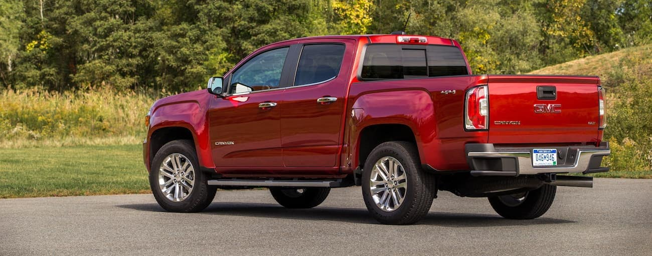 A red 2020 GMC Canyon is shown from the rear in front of trees near Atlanta, GA, and may look similar to the 2021 Elevation.