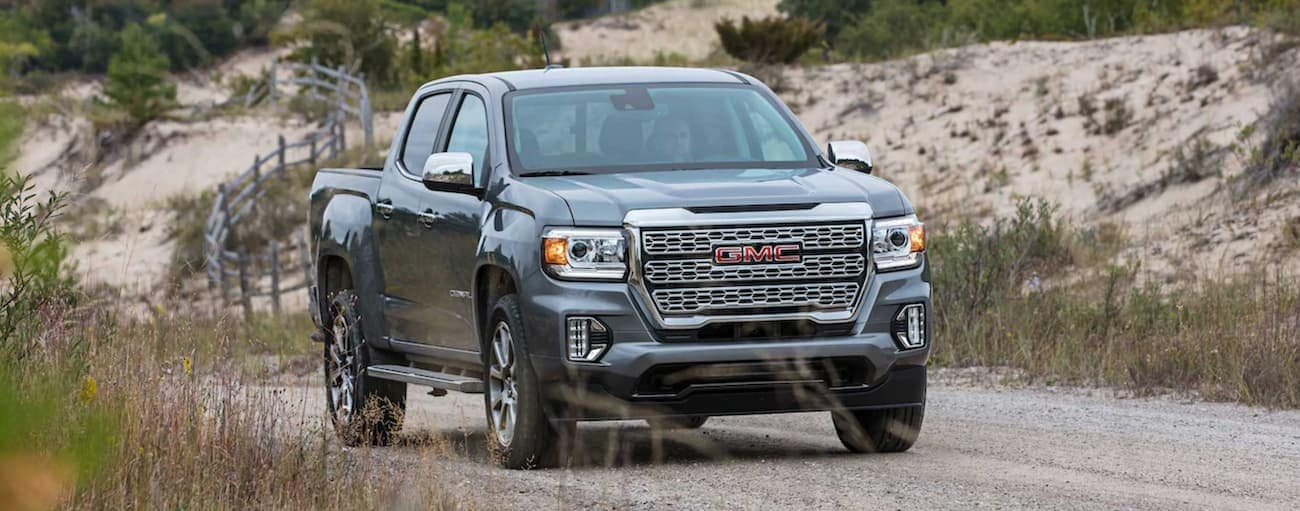 A grey 2021 GMC Canyon Denali is driving on a gravel road.