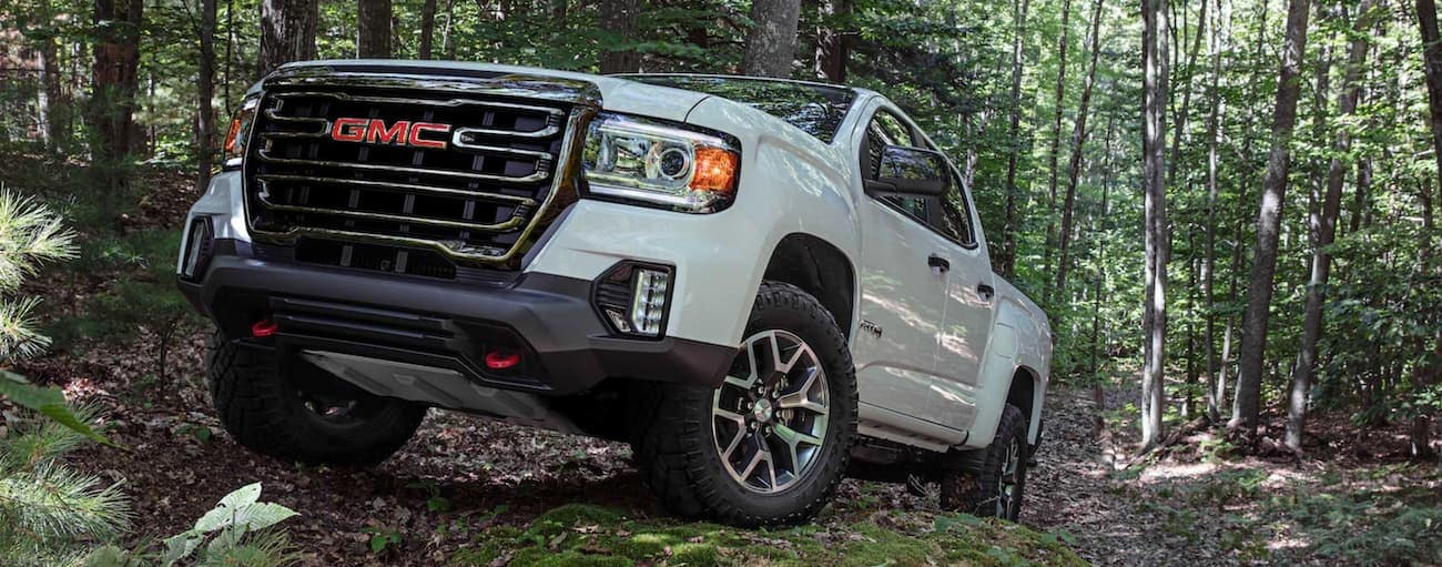 A white 2021 GMC Canyon AT4 is off-roading in the woods.