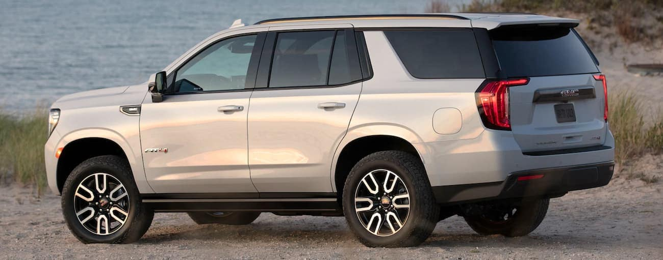 A white 2021 GMC Yukon AT4 is parked on the beach.