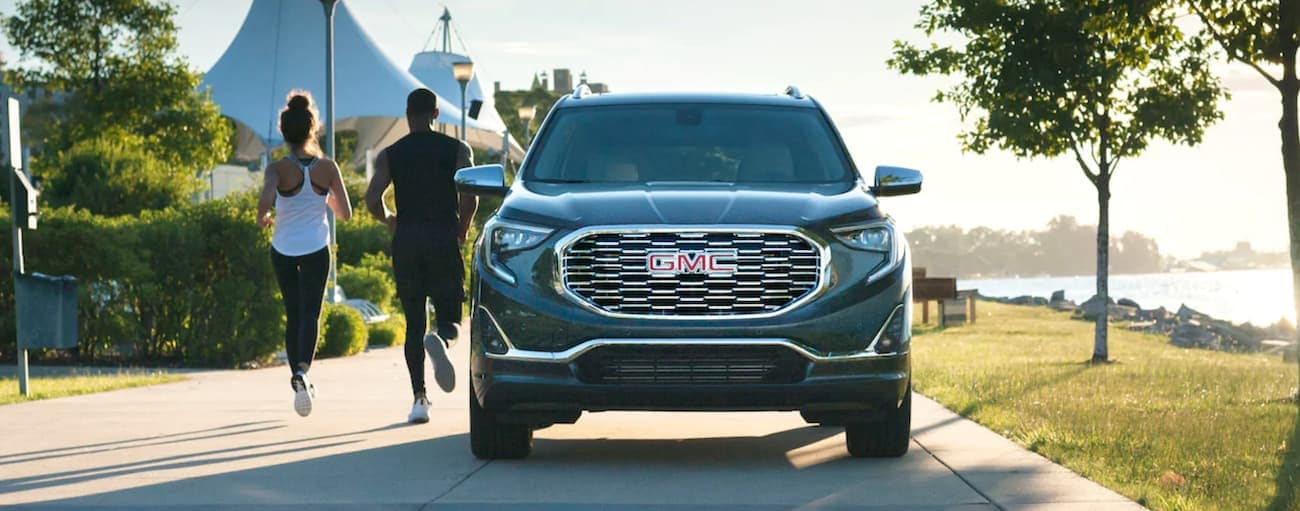 A couple is jogging away from a grey 2020 GMC Terrain parked next to a lake.