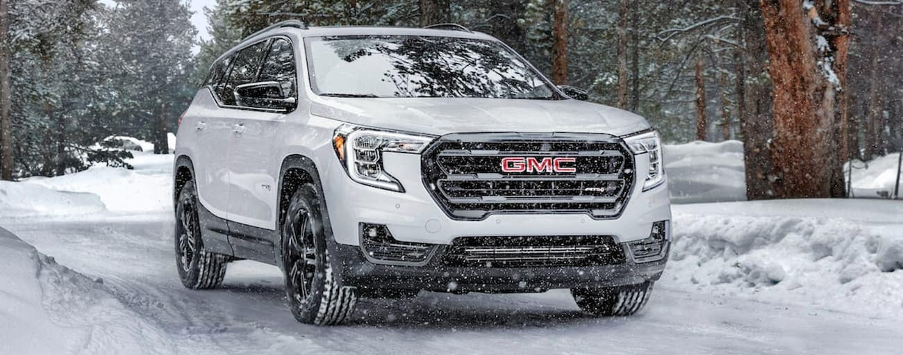 A white 2021 GMC Terrain is driving on a snowy road.