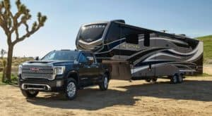A black 2020 GMC Sierra 2500, which is popular among GMC Trucks, is parked in a desert with a large camper.