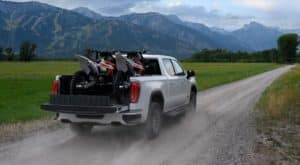 A white 2020 GMC Sierra 1500 AT4 is on a dirt road with dirt bikes in the bed.