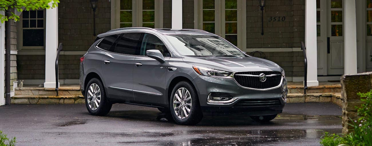 A gray 2020 Buick Enclave is parked in front of a nice house outside Atlanta, GA.