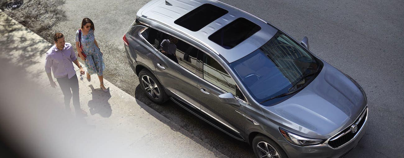 Two people are waking towards a gray 2020 Buick Enclave that is parked on a street, shown from above.