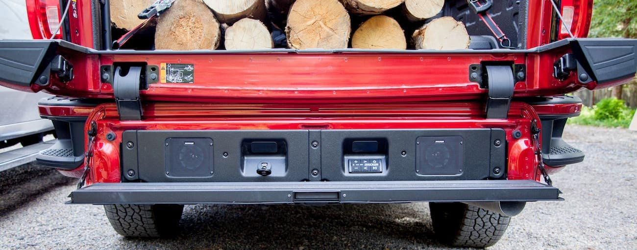 A closeup is shown of the MultiPro tailgate on a red 2020 GMC Sierra 2500 AT4 which also has wood in the bed. This tailgate wins in the 2020 GMC Sierra 2500 vs 2020 Ford F-250 comparison for Atlanta drivers.