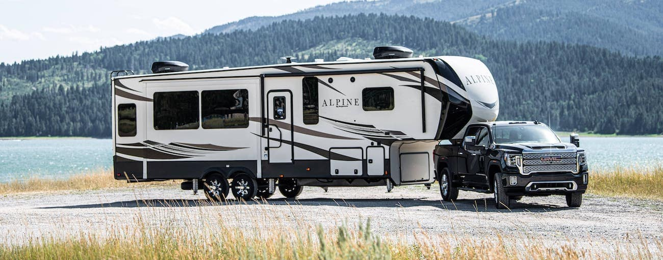 A black 2020 GMC Sierra 2500 Denali is towing a large camper in front of mountains and a lake.