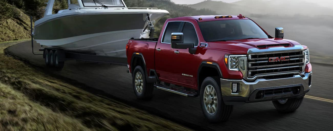 A red 2020 GMC Sierra 2500, which wins when comparing the 2020 GMC Sierra 2500 vs 2020 Ram 2500, is towing a boat.