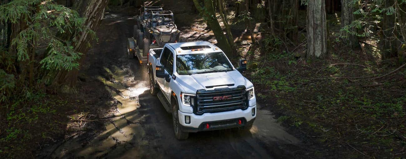 A white 2020 GMC Sierra 2500 AT4 is towing side-by-sides on a trail outside Atlanta, GA.