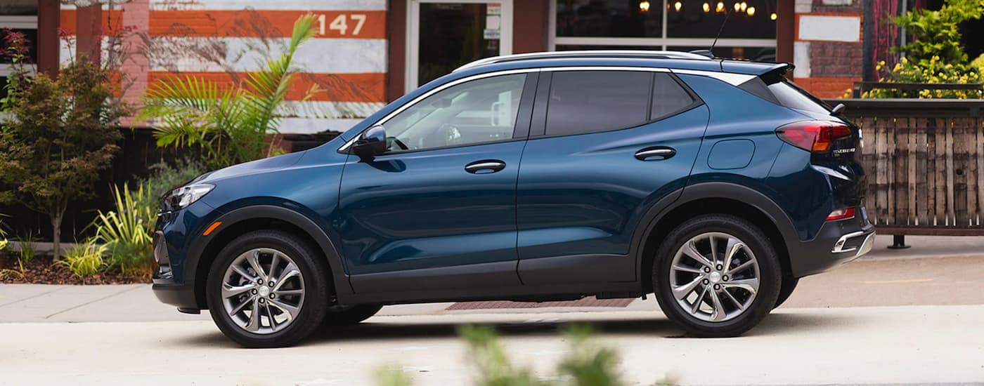 A blue 2020 Buick Encore GX is shown from the side in front an orange and white building.