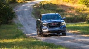 One of the common used trucks at your local dealership, a gray 2017 GMC Sierra All Terrain SLT is driving on a rural dirt road outside Atlanta, GA.