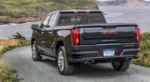 The rear is shown of a dark blue 2020 GMC Sierra 1500 Denali on a coastal road.