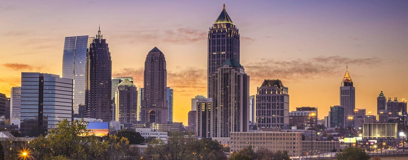 The Atlanta skyline is shown at sunrise against a purple and yellow sky.