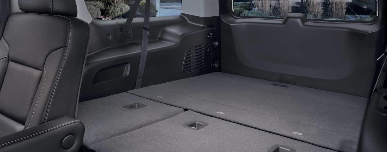 The folded down cargo area of a 2020 GMC Yukon is shown.
