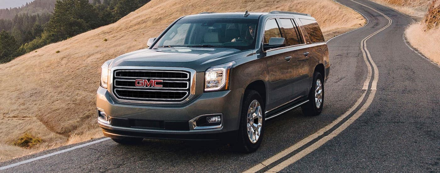A gray 2020 GMC Yukon is driving on a winding road.