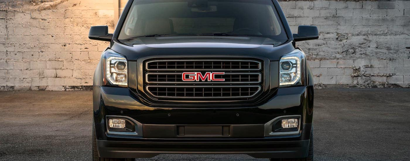 A black 2020 GMC Yukon is shown from the front while parked in front of a cinder block wall near Atlanta, GA.