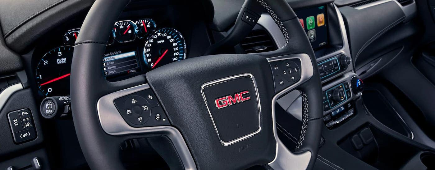 A closeup is showing the steering wheel and interior of a 2020 GMC Yukon, winner of the 2020 GMC Yukon vs 2020 Ford Expedition comparison.